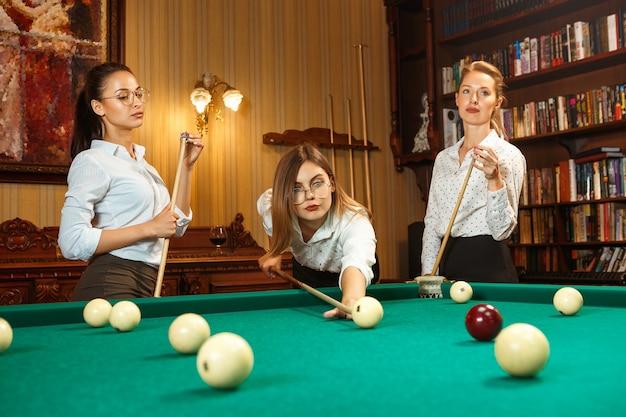Jonge glimlachende vrouwen die na het werk biljart spelen op kantoor of thuis. zakencollega's die zich bezighouden met recreatieve activiteiten. vriendschap, vrijetijdsbesteding, spelconcept.