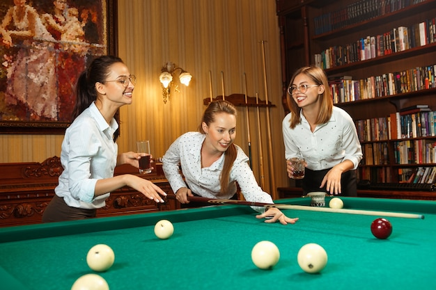 Jonge glimlachende vrouwen die na het werk biljart spelen op kantoor of thuis.