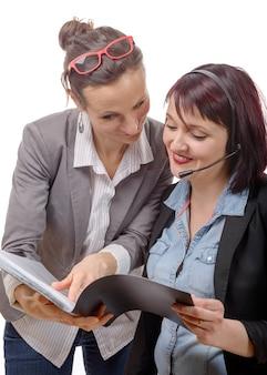 Jonge glimlachende vrouwen die samen met notitieboekje werken
