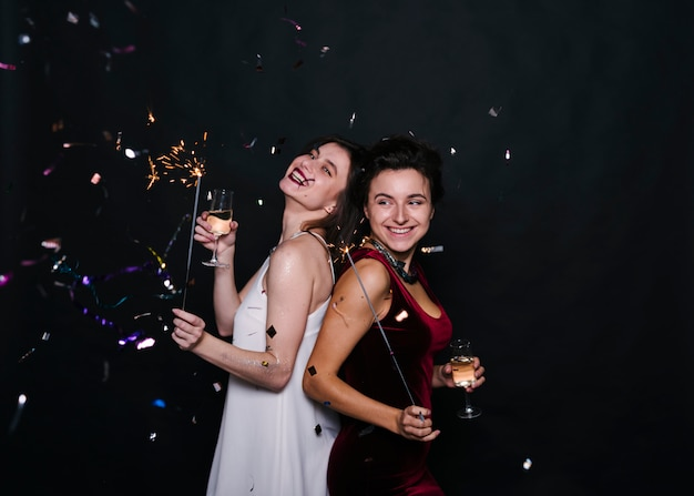 Jonge glimlachende vrouwen die zich rijtjes met de lichten en de glazen van bengalen bevinden