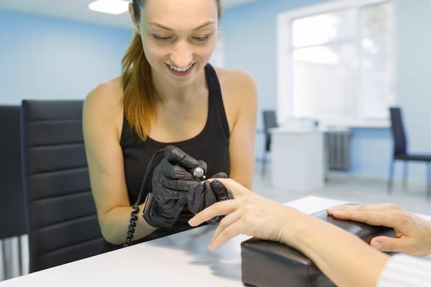 Jonge glimlachende vrouwenschoonheidsspecialist in schoonheidsspijkersalon