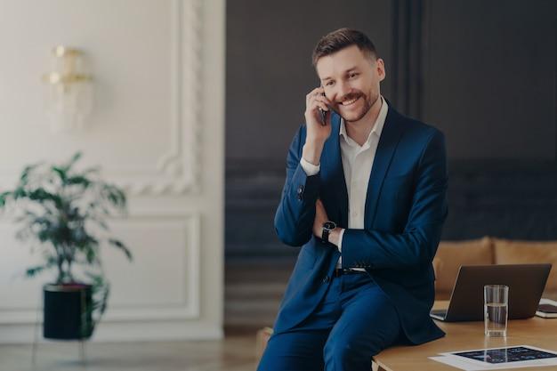 Jonge glimlachende zakenman in formeel donkerblauw pak die aan de telefoon praat in een stijlvol kantoor en blij is om goed nieuws te horen terwijl hij op het bureau zit met laptop, projectfoto's en glas water