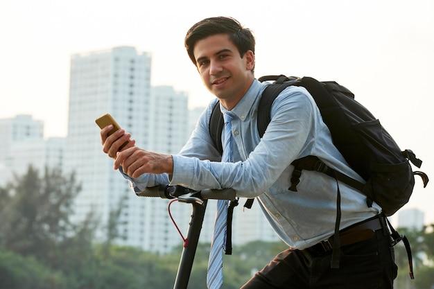 Jonge glimlachende zakenman met grote rugzak