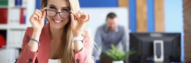 Jonge glimlachende zakenvrouw die een bril in kantoor aanpast