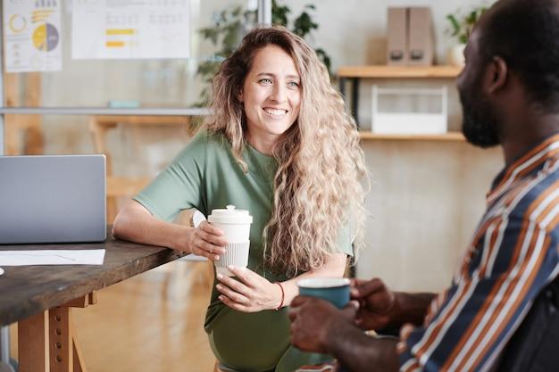 Jonge glimlachende zakenvrouw die koffie drinkt met haar collega op kantoor tijdens de koffiepauze