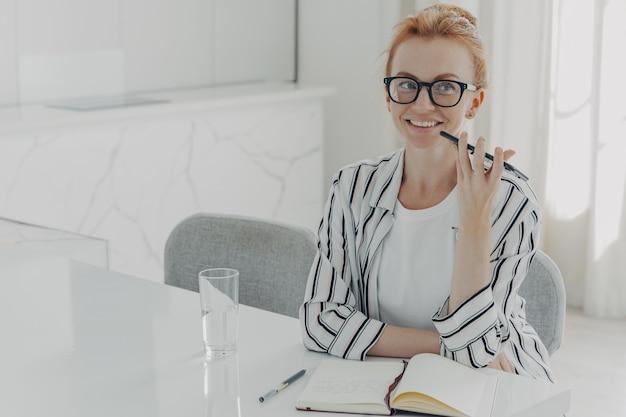 Jonge glimlachende zakenvrouw met behulp van de stemassistent-app op een smartphone die thuis aan tafel zit