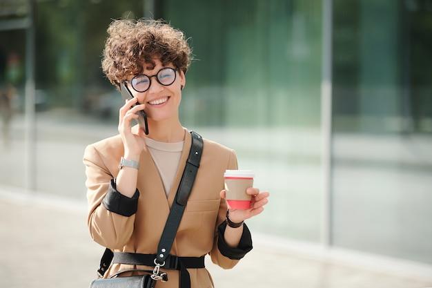 Jonge glimlachende zakenvrouw met een drankje die smartphone op het gehoor vasthoudt terwijl ze de klant aan de telefoon raadpleegt tegen de buitenkant van het moderne gebouw