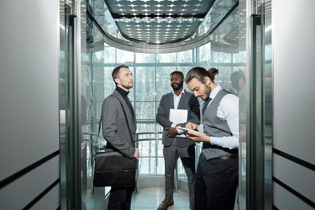 Jonge, goed geklede mannelijke ondernemer met behulp van tablet in de lift van het moderne zakencentrum onder zijn collega's