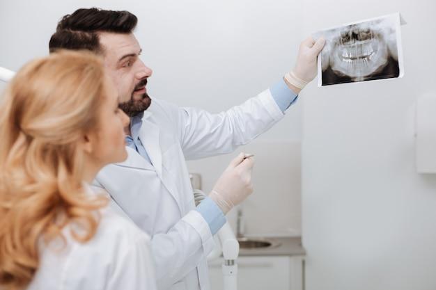 Jonge, goed opgeleide arts die professioneel advies vraagt aan collega-arts terwijl hij op zoek is naar de kern van het probleem en een röntgenfoto voorhoudt