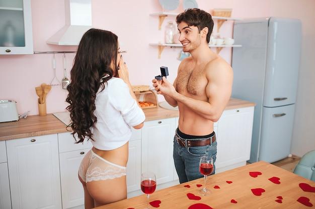 Jonge goedgebouwde man staat in de keuken en maakt poropositie naar de vrouw. ze ziet er blij en opgewonden uit. man houdt ring in vak voor vrouw.