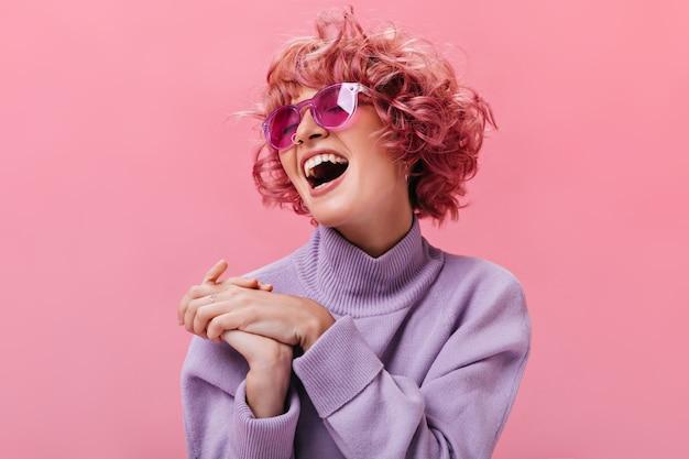 Jonge goedgehumeurde krullende vrouw in fuchsia zonnebril en paarse kasjmier trui lacht op geïsoleerde roze muur