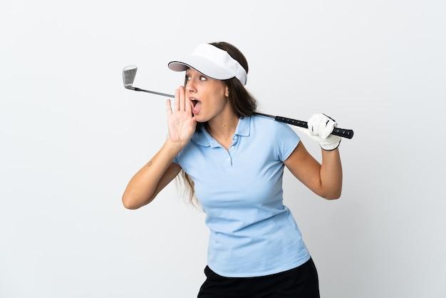 Jonge golfervrouw over geïsoleerde witte achtergrond die met wijd open mond naar de zijkant schreeuwt