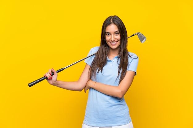 Jonge golfspelervrouw die over geïsoleerde gele muur omhoog terwijl het glimlachen kijkt