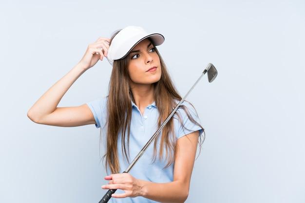Jonge golfspelervrouw over geïsoleerde blauwe muur die twijfels hebben en met verwarring gezichtsuitdrukking