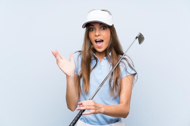 Jonge golfspelervrouw over geïsoleerde blauwe muur met geschokte gelaatsuitdrukking