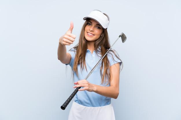 Jonge golfspelervrouw over geïsoleerde blauwe muur met omhoog duimen omdat er iets goeds is gebeurd