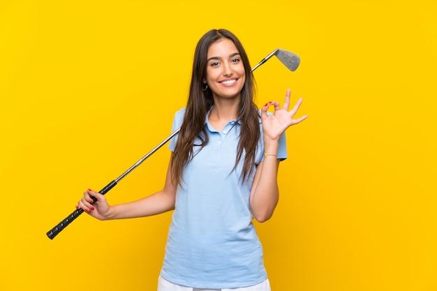 Jonge golfspelervrouw over geïsoleerde gele muur die ok teken met vingers tonen