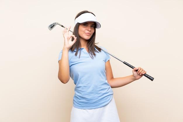 Jonge golfspelervrouw over geïsoleerde muur die ok teken met vingers tonen