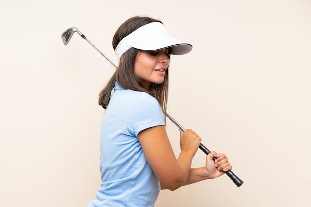 Jonge golfspelervrouw over geïsoleerde muur