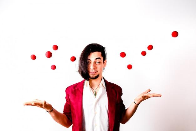 Jonge goochelaar die rode luchtballen werpt om geluk te zoeken.