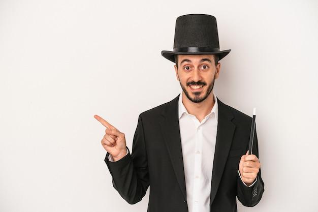 Jonge goochelaar man met toverstaf geïsoleerd op een witte achtergrond glimlachend en opzij wijzend, iets tonen op lege ruimte.