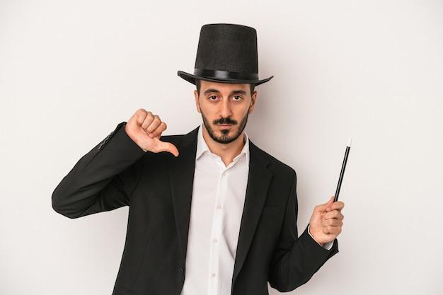 Jonge goochelaar man met toverstaf geïsoleerd op een witte achtergrond met een afkeer gebaar, duim omlaag. onenigheid begrip.