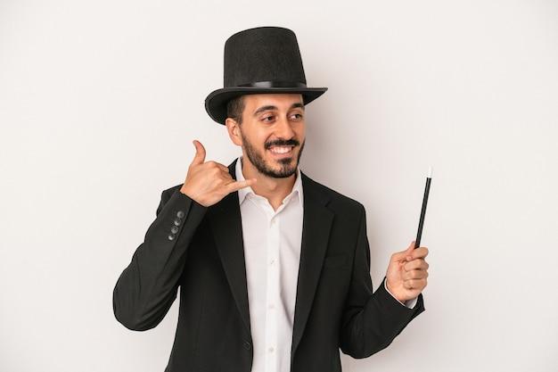 Jonge goochelaar man met toverstaf geïsoleerd op een witte achtergrond met een mobiel telefoongesprek gebaar met vingers.