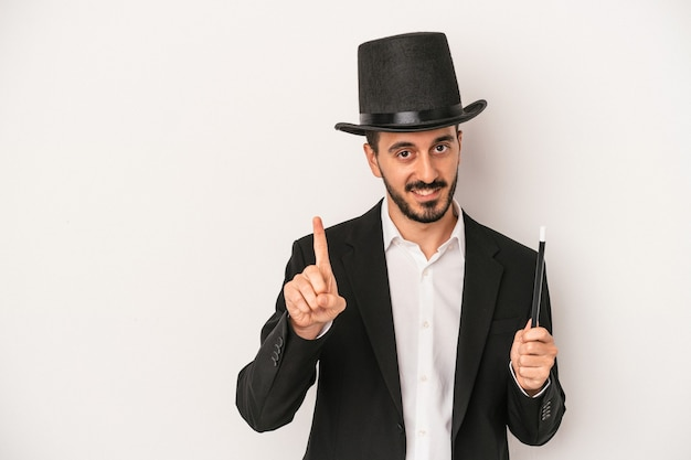 Jonge goochelaar man met toverstaf geïsoleerd op een witte achtergrond met nummer één met vinger.