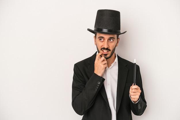 Jonge goochelaar man met toverstaf geïsoleerd op een witte achtergrond ontspannen denken over iets kijken naar een kopie ruimte.
