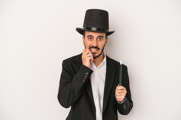 Jonge goochelaar man met toverstaf geïsoleerd op een witte achtergrond vingernagels bijten, nerveus en erg angstig.