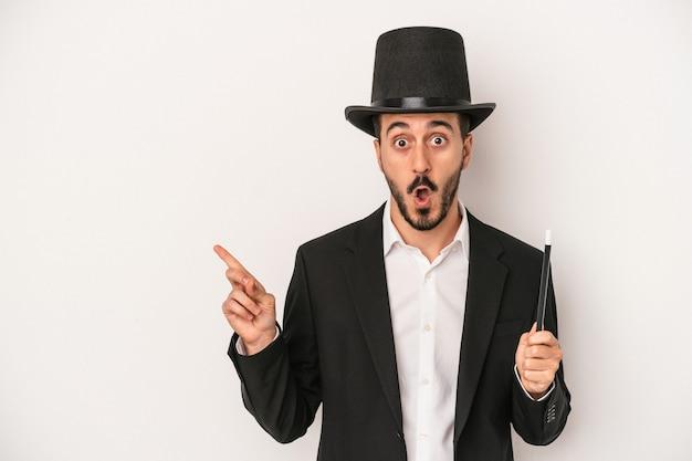 Jonge goochelaar man met toverstaf geïsoleerd op een witte achtergrond wijzend naar de zijkant