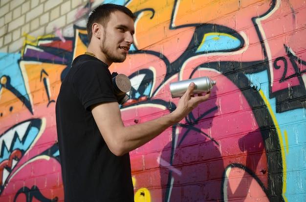 Jonge graffitikunstenaar met rugzak en gasmasker op zijn nek schildert kleurrijke graffiti in roze tinten op bakstenen muur. straatkunst en hedendaags schilderproces