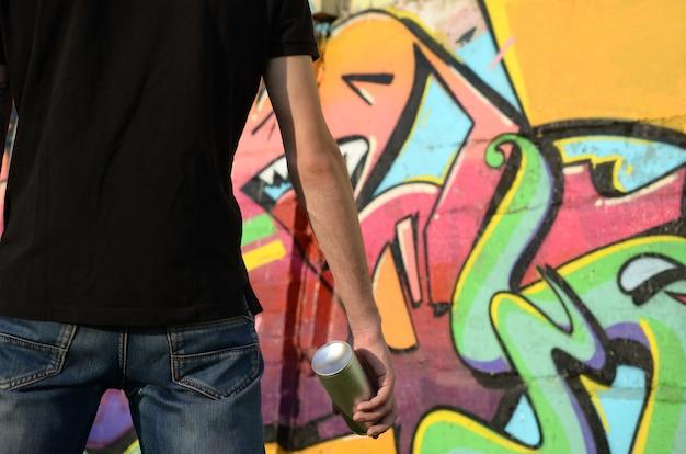 Jonge graffitikunstenaar met rugzak en gasmasker op zijn nek schildert kleurrijke graffiti in roze tinten op bakstenen muur