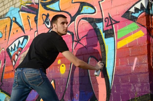 Jonge graffitikunstenaar met rugzak en gasmasker op zijn nek schildert kleurrijke graffiti in roze tinten