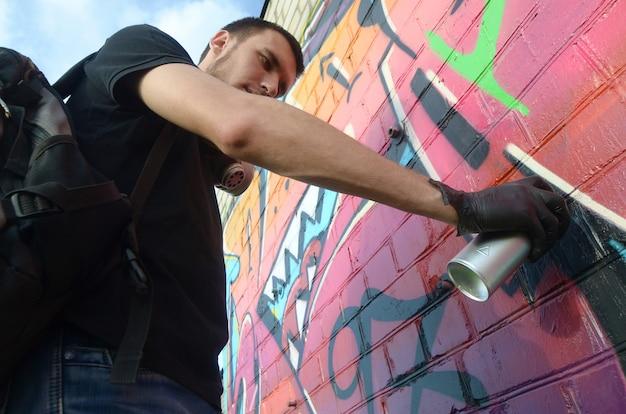 Jonge graffitikunstenaar met rugzak en gasmasker op zijn nek schildert kleurrijke graffiti