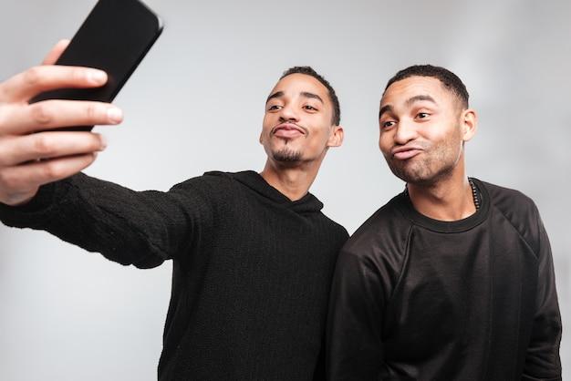Jonge grappige afrikaanse mannen maken een selfie.