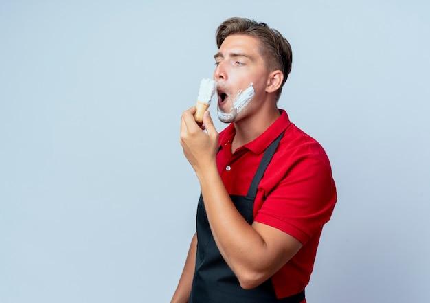 Jonge grappige blonde mannelijke kapper in uniform uitstrijkjes scheerschuim op gezicht kant kijken
