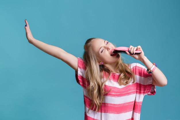 Jonge grappige blonde vrouw zingt met roze haarborstel op blauwe achtergrond