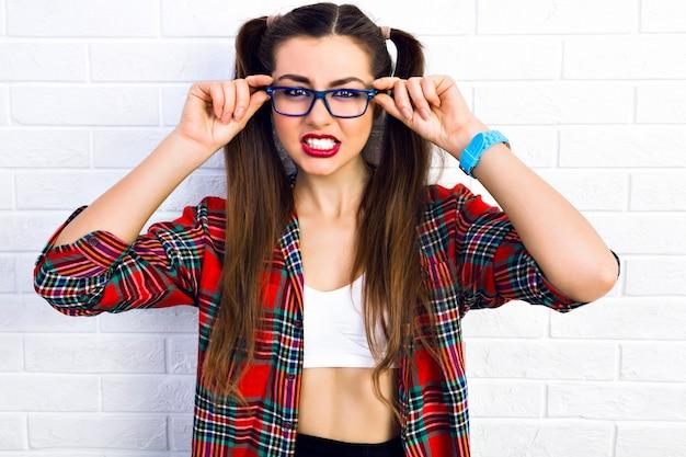 Jonge grappige brutale vrouw, maakt grappig boos gezicht, toont haar tanden, lichte make-up, lange butte haren, hipster bril en geruite hemd, gek alleen.