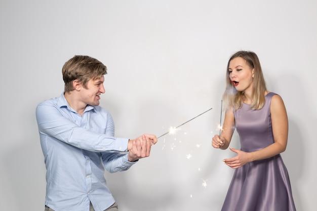 Jonge grappige gelukkige paar met wonderkaarsen gek rond