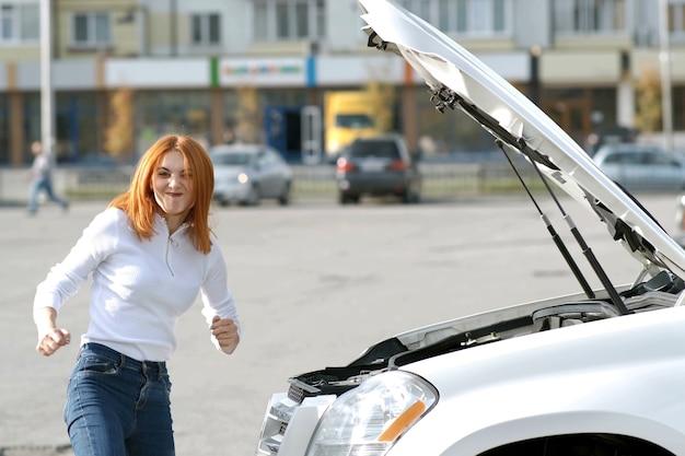 Jonge grappige glimlachende vrouwenbestuurder dichtbij kapotte auto met geknalde kap met een pechprobleem