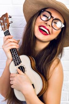 Jonge grappige hipster vrouw met plezier en spelen op kleine ukelele gitaar, zingen en dansen. vintage bril en strooien hoed dragen, vreugde, positieve stemming.
