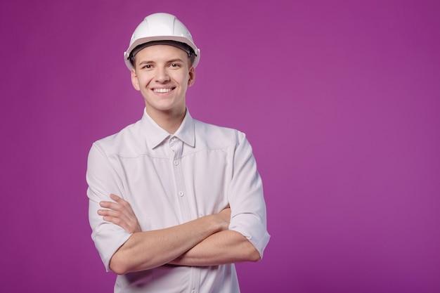 Jonge grappige lachende man in witte helm op paarse achtergrond