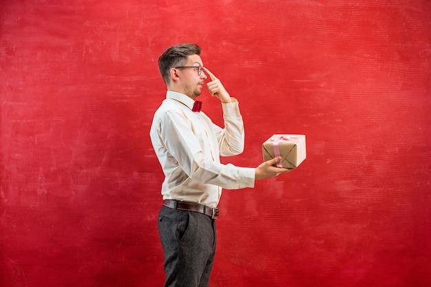 Jonge grappige man met cadeau op rode studio