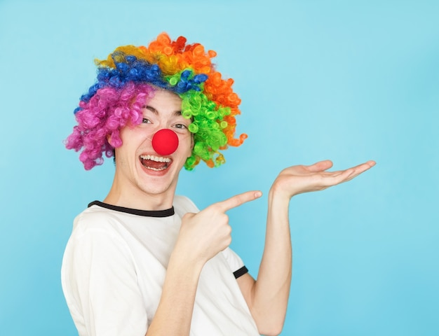 Jonge grappige mannelijke tiener in wit t-shirt op blauw in clown pruik