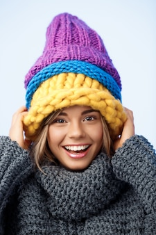 Jonge grappige mooie blonde vrouw in gebreide hoeden en trui lachend op blauw.