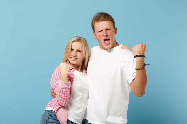 Jonge grappige paar vrienden man en vrouw in wit roze lege lege t-shirts poseren