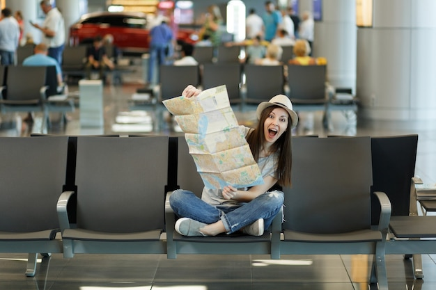Jonge grappige reizigerstoeristenvrouw met gekruiste benen die papieren kaart vasthoudt, route zoekt, wachtend in de lobby op de internationale luchthaven