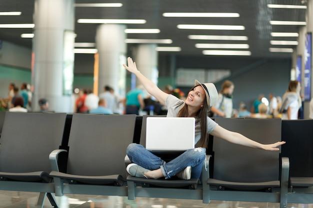 Jonge grappige reizigerstoeristenvrouw met laptop zit met gekruiste benen die handen spreiden als tijdens de vlucht, wachtend in de lobby op de luchthaven