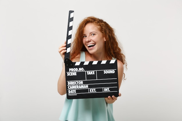 Jonge grappige roodharige vrouw meisje in casual lichte kleding poseren geïsoleerd op een witte muur achtergrond in de studio. mensen levensstijl concept. bespotten kopie ruimte. klassieke zwarte film filmklapper vasthouden.